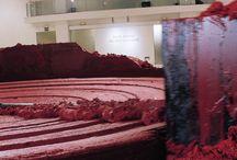 Anish Kapoor / My Red Homeland (2003), consistente en un círculo de 12 metros de diámetro, 25 toneladas de cera y vaselina coloreada en rojo, un motor hidráulico y un brazo de acero en constante movimiento que va dando forma a la materia.