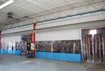 Industrial Curtain Walls / Heavy vinyl curtains are used to divide warehouse space, prevent contamination and maintain temperature zones within a facility. Most often they are used with a steel roller track system to retract and offer flexibility in how you use the space. Industrial Curtain Walls are designed as a curtain room divider or an enclosure for clean room applications.