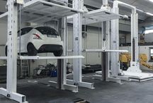 VEGA Car lift, dependent double stacker / Ecospace has realized VEGA, a new model of car litf, characterized by two overlapping platforms, raised by special cylinders. Six models of VEGA were sold to McLaren Automotive headquarter in Woking (UK), for the storage of P1 McLaren new models.
