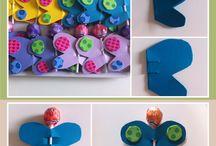 Birthday's favors / Prendere del cartoncino formato A4 e piegarlo in due. In un cartone creare la sagoma di una farfalla con altezza 8 cm. Ritagliarla e usarla sul cartoncino colorato. Disegnare 3 farfalle sul lato piegato. Ritagliare la sagoma e praticare due tagli con la forbice. Aprire la farfalla e inserire un lecca-lecca. Decorare le ali a piacere.