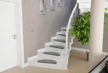 Schody Białe / Schody dywanowe to doskonały wybór dla osób, które cenią sobie minimalizm zawierający prostą i oszczędną formę. Ten rodzaj schodów idealnie nadaje się do nowoczesnych wnętrz zapewniając jednocześnie bezpieczeństwo osób je użytkujących. Względnie prosta budowa schodów dywanowych powoduje, że przypominają dywan spływający po niewidocznych stopniach - stąd ich potoczna nazwa.