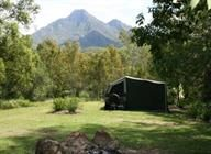Camping / The Mt Barney Lodge campground has grassed and shaded camp sites with campfire circles, creek frontage and spectacular mountain views.