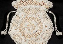 """Reticule / a woman's small handbag, originally netted and typically having a drawstring and decorated with embroidery or beading. Also called a """"reticle."""""""