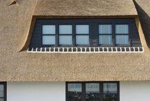 Presolid | Een –bijna- dorpje aan de Rijn / Wat krijgen we nu? We zijn op zoek naar de Presolid Home woning van Wil en Jan en we krijgen er een –bijna- dorp bij! Dit is onmiskenbaar Oegstgeest aan de Rijn en aan één van de oevers bevindt zich het dubbelcomplex van de trotse eigenaars. Dit witte, rietgedekte landhuis, lijkt met haar eigen omschrijving te 'worstelen': dit land-huis is immers bijna een water-huis.