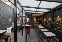 Lauriston Road Bakery / Victoria Park Village in east London is the setting for this new neighbourhood bakery. A 'light touch' renovation of an old restaurant, many of the existing features were retained and refurbished, including the bi-folding shopfront and courtyard garden.  A simple palette of dark grey tiles and painted brick is complemented by bespoke handmade clay pendant lights, limed ash joinery and hand drawn floral murals.