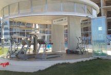 Cerramiento de Terraza con Cortinas de Cristal / Acristalamiento de la terraza de un edificio que alberga un gimnasio en su interior para que puedan tener los usuarios unas vistas panorámicas
