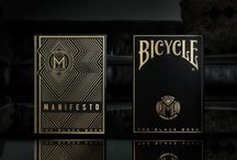 """The Black Book Manifesto Gold Edition & [A]rchive / A Limited Gold Edition of the Black Book Manifesto designer Playing Cards.  Paired with the [A]rchive - Solid. Clear. Built to display a five-sided view and fit a 5"""" x 7"""" frame. A solid clear acrylic core with an acrylic Museum grade cover. What's on your wall?"""
