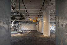 """KIITO 公共施設オープン・リノベーション / 内部空間の白い楕円のフレームを組み合わせたディスプレイ什器は「繭」をイメージしたもの。「KIITO」がもともと、1927年に輸出生糸の品質検査を行う神戸市生糸検査所として建てられた建物であることを踏まえたデザインだ。""""繭""""が空間内に点在する様子は日本庭園や枯山水をイメージさせる。「KIITO」が元から持つ床や壁の力強く、荒々しいディテールの中で、繊細なフレームの細いラインが浮遊感と透明感を演出し、作品が鮮明にフォーカスされる。ニュートラルなデザインで、ショップでは気軽に購入できる価格のものから前衛的なもの、熟練の作家による一点ものまで幅広い製品が違和感なく並べられる。ギャラリーも、若手から熟練作家のアート作品まで幅広いジャンルがそれぞれに引き立つように並べられる。  同じく繭をデザインコンセプトにした照明が柔らかい光で空間を照らす。  繭は生命を育むものの象徴だ。繭からとられた糸が美しい生糸や絹織物に生まれ変わるように、神戸港を通じて日本に、そして世界に日本のデザインの美を送り届ける施設となる。"""