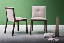 Sedie - Esedra / Esedra è una sedia con struttura in legno massello, seduta e schienale imbottiti. La forma regolare della struttura supporta dei pannelli imbottiti particolarmente sottili ma confortevoli.
