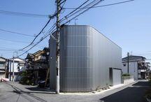鳳の家 House In Otori / [光も風も入るシルバーの壁] 大阪府堺市の住宅密集地に建つ木造2階建ての住宅。「プライバシーを確保しつつ、風と光を取りこむ居心地の良い住まい」がここに住むご夫婦の要望だった。またビルトインガレージの設置も優先順位が高かった。  そこで私たちが出した回答は、シルバーのガルバリウム板で全体を覆うデザインだった。一見閉鎖的だが、窓や駐車スペースの存在感がなく、外からは生活の様子がうかがえない。  風を通す工夫として外壁の一部、道路側と中庭側の2カ所にガリバリウム板と似た質感や色のスリット板を2枚、互い違いに並べた。視線を遮りつつ、通風を確保している。  採光については、2つの中庭とドライスペースを少し離して配置し、それぞれに大きな窓を開けた。分散された中庭とドライスペースを通じて、1階にも2階にもたっぷりと光が入る。この心地よくオープンな中庭は各部屋から眺めることができる。  建て坪約13坪、決して広いとは言えない上に敷地の外周が塀で囲まれている住宅だが、内部ではそんなことを意識させない開放感と広がりを感じさせる。プライバシーもしっかりと守る居住空間だ。