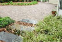 Stepping Stone Garden Design / This backyard space in Avondale, Florida went from being a jumble of different plants to an outdoor space you really want to spend time in. 5 Star Outdoor Design designed this outdoor space with a curved patio leading to a seating wall that complements the unique stepping stone path. The beautifully arranged landscape really help make this space wonderful.