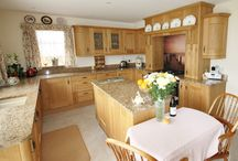 Gosfield - Oak Shaker Kitchen with statement splash back / Oak Shaker, granite worktop in 'oro Veneziano', statement image glass splash back, picture of a Jetty at Coniston Water in Cumbria, clients have actually been there themselves. Designed, Supplied and Installed by KITCHENCRAFT.