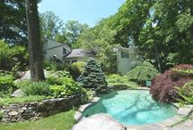 49 Sumner Road, Greenwich CT / Nature's backdrop and mature plantings set the perfect stage for this easy living home. Large windows invite natural light and garden views in and are highlighted through the living room, dining room and great room with soaring ceiling. A master suite located up its own short staircase offers privacy; three bedrooms are on the first floor. Two room suite with full bath with its own private entrance can be used as a guest suite or office. Lovely natural inground pool.