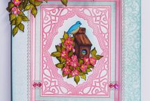 Birds & Blooms Collection / The Birds and Blooms Collection features garden scenes, bluebirds, blooming branches, picket fences, bird baths, bird houses, butterflies and frilly hydrangeas. Designer papers include dozens of card fronts, pre-designed layouts, borders, and sentiments. Six hand-drawn stamp sets feature blossom laden branches, nesting birds, garden scenes and an elegant collage. Two sets of dies coordinate with papers and stamps allowing you to add realistic blossoms, branches and birds to your artwork.