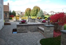 Backyard Paradise in Naperville, IL / Here are some photos of a recent project we completed in Naperville. We provided the homeowners with a patio space, fire pit, built-in BBQ and a unique water feature all combined into one large space. The water feature is a large planter with two waterfalls built into it, which empty in a moat that surrounds the patio. It was built with Unilock Brussels Block pavers, natural bluestone inlay and Unilock Olde Quarry walls.