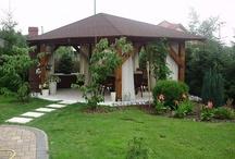 Altana ogrodowa / Czujesz, że czegoś brakuje w twoim ogrodzie? Postaw na altanę ogrodową! Drewniana altanka z pnączami winogron będzie twoją świątynią, w której naładujesz akumulatory po trudnym dniu. Sprawdzi się również jako miejsce do rodzinnych spotkań. W budowie wymarzonej altany ogranicza cię jedynie wyobraźnia- możesz stworzyć drewniany zadaszony pawilon lub postawić na otwartą przestrzeń wykonanej z metalu pergoli.