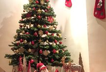 Christmas home decor / Cosy home decoration for Christmas with Christmas tree decorated with red and gold ornaments and decorations including candle christmas trees, deers, Santa Clause and gift packages