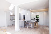 Rear/Side Extension for a terraced house in Hampton / An astonishing white & grey spacious kitchen with plenty of light from the veluxes brilliantly accomplished with white vintage pendants lighting