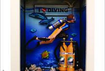 Quadro Scuba Diving / Tamanho 22 cm L x 9 cm P x 24,5 cm H. Elaborado em mdf e acabamento acetinado branco. Criação e desenvolvimento digital do papel de parede, uso de madeira balsa, imãs de geladeira, caramujos marinho naturais, mergulhador e cilindros de plástico.
