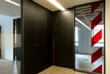 Uffici Ance / Predomina negli interni la scelta di materiali ruvidi e di semi-lavorati; la grafica delle strisce rosse di segnalazione, gli impianti, i corrugati, i tamburati, le strutture in cemento armato lasciate a vista, contribuiscono all'immagine coordinata del brand Ance