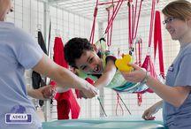 Terapie: MFE – Multifunctional Exercise Unit / L'unità multifunzione, composta da una panca, un sistema di pulegge e corde, è un attrezzo estremamente versatile che può essere usato in vari modi a beneficio dei pazienti affetti da disturbi neurologici. La MFE sfrutta l'azione dei pesi resistivi per potenziare i muscoli e rimandare al cervello il movimento corretto di ciascun arto.