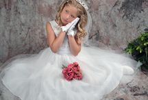First Communion Dress of the Day D1217 / Dress of the Day! This beautiful first communion dress is tea length and made of satin and organza. Its fully lined and has satin ribbons on waist and satin tie back. Priced at only $49.95 and made in the USA.