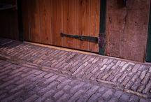 Renovatie klinkervloer molen de Zandhaas Santpoort-Noord / In molen de Zandhaas uit 1779 hebben we de eeuwenoude klinkervloer gerenoveerd. Hierbij zijn unieke details en gebruikssporen bewaard gebleven.