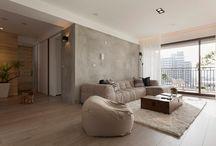 Apto_sala / Chão e paredes em cimento queimado, porém, tons diferentes e móveis em madeira.