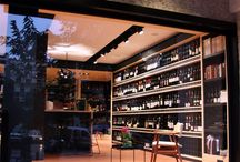 """Mr Vertigo wine shop / The functional lighting of Mr Vertigo wine shop gives a more dramatic feeling to the space and brings the visitor-consumer into a """"cellar"""". The decorative lighting, is connected to Paul Auster's novel """" Mr Vertigo"""", with his protagonist flying, like the round Santorini vine in the center of the store."""