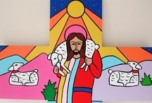 Jesus and the Lambs / This wooden crucifix was created and painted for a Catholic School in Erith Kent. The image features Jesus and his flock both above and below. I replicated this simple cross from a small 6 inch high wooden crucifix that existed in the school. The cross now features in a stairwell of the school.