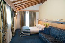 Le nostre Camere... / I nostri ospiti possono scegliere tra diverse tipologie di camere, che variano in dimensioni, ubicazione ed arredi. Gli interni eleganti ed accoglienti, derivanti dal mix eclettico di materiali preziosi, tra cui specchi, ottone, marmo, pietra nera e legno, si fondono in un comfort caldo, rendendo l'Hotel Alexander unicamente affascinante e regalando il piacere di una vacanza rilassante ed in stile.