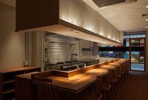 日松亭 nisshoutei / [内外を柔かく区切るガラスのファサード] 大阪下町の商店街で長年、親しまれてきた洋食屋。先代から若夫婦に代替わりするタイミングでリニューアルした。  店内はカウンターがメインのフルオープンキッチン。奥にテーブルが4席ある。先代へのオマージュを込めて外装のレンガはそのまま残した。ファサードはお客が入りやすいようにほぼ全面がガラスになっているが、シェフやお客が外からの視線を気にせずに食事を楽しめるよう、店名が入った黒い帯を配した。   床は外装と同様、先代からの記憶を引き継ぐレンガを使った。ただし外装と貼り方は変えて違いを出している。壁と天井は客席では白を、トイレがある奥のほうは黒を基調にして空間にリズムをつけた。  オーナーの隣にはいつも奥様がいて、お客との自然な対話を楽しんでいる。家庭的な雰囲気を感じさせる木のカウンターと椅子で、これからも地元に根付いていけるよう営まれている。