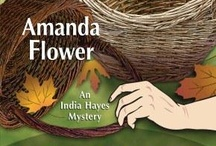 """India Hayes Mysteries / By Amanda Flower Maid of Murder: Agatha Award Nominee for Best First Novel """"Flower's breezy debut introduces a quirky heroine...Warring cats and distinctive characters, like India's 'everything Irish' landlady and her bizarre '60s activist parents, will appeal to cozy fans."""" -Publishers Weekly.  Murder in a Basket: """"In Flower's delightful, clean-as-a-whistle second India Hayes mystery. . . The satisfying conclusion will leave cozy fans eager for India's next adventure.""""- Publishers Weekly."""
