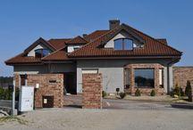 Projekt domu Siedziba / Projekt domu Siedziba, to komfortowy dom dla 4-5 cioosobowej rodziny. Łączy w sobie elementy tradycyjnej architektury z nowoczesnością. Atrakcyjna, rozbudowana bryła domu z lukarnami, z wykuszowym oknem jadalni, tarasem z pergolą, czy podcieniem wejściowym połączone są w harmonijną całość. Daje ona wrażenie stabilizacji i spokoju.