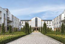 Nasze realizacje - Dom Zakonny Zgromadzenia Księży Marianów / Budynek klasztoru jest zlokalizowany w bliskim sąsiedztwie Bazyliki Licheńskiej. Obiekt ten ma formę dostojną, budzącą szacunek, a jednocześnie skromną i oszczędną w przestrzennych środkach wyrazu. Dom zakonny w kontekście bazyliki jest skromny ale posiada swój własny indywidualny charakter. Budynek klasztoru jest 4-kondygnacyjny, podpiwniczony, z użytkowym poddaszem. Obiekt ten został wykonany w technologii tradycyjnej - murowany, dach wielospadowy – więźba drewniana.