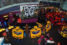 Transformers Human Alliance / Partner with your favorite Transformers (Optimus Prime, Bumblebee and Sideswipe), as you battle your way across the world, destroying Decepticons. 2 players can sit inside the Bumblebee-themed game-cabinet. Defend entire cities as part of the Human Alliance, and bring an end to evil.