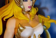 She-Ra - The Princess of Power / She-ra - the Princess of Power, 1/6 scale 30cm height. The flowing hair, the dress, cape, helmet, armbands and banners, the magic sword, belt and boots have been entirely shaped by hand. Helmet, suit and swords were embellished with stones with glitter transparent effect. EVERYTHING 'INTENDED EXCLUSIVELY FROM FANDOMKASTOM. If will be achieved at least 5 reservations will be created copies.