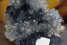 los minerales / Nombre:Galena. Forma:Triangular. Color:Gris Plomo. Raya:Gris Oscuro. Brillo:Metálico. Exfoliación:Cúbico Perfecto. Dureza:2.5 en la escala de Mohs (Muy blando). Formula Química:PbS. Densidad:7.5 g / cm3. Curiosidades:La Galena ya era conocida por los Ejípcios 3000 años a.C.La usaban los Romanos y Griegos en tuberias de agua, revestimientos y placas.