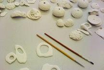 Herstellungsprozess / Mein Schmuck besteht aus edler Keramik. Ich stelle sie selbst her. Nach maritimen Fundstücken entwickle ich Formen und vollende sie in Montblanc-Porzellan. Flüssiges Porzellan wird in Gipsformen gegossen. Die daraus entstehenden Teile werden bearbeitet und nach dem Trocknen gebrannt. Nach diesem Brand können die Porzellanteile geschliffen und glasiert werden. Schlussendlich findet der Glasurbrand statt (1350 ºC), bei dem die Festigkeit und niedrige Porosität des Porzellans entsteht.
