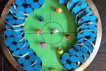 Traktatie crèche voetbal / Liga's ingepakt in aluminiumfolie en een voetbal getekend en erop geplakt. En een voetbalveld met gogo's en sateprikkers.