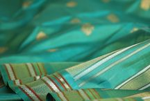 Buttidar: Sari Adorned /  In Buttidar, Kanakavalli brings you the kanjivaram, adorned. Each exquisitely detailed sari in this curation features motifs presented in repeat patterns, rendered in varied forms to create a rhythmic geometry on the drape. The buttis - tiny, delicate motifs or larger and more striking in relief - are woven in fine zari to dot the body of the sumptuous silks, or occasionally set within checks. This collective reveals the beauty that lies in the nuance of the kanjivaram's embellishment.
