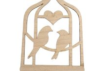 Timber-Treasures love birds laser cut decoration / Our laser cut decorations are perfect for hanging around the house. Combining the natural grain of the wood with the precise and detailed laser cut designs, our decorations are delicate and beautiful and suitable to be hung in any home. Each decoration has an attached ribbon so the decoration can be hung at ease. This particular design is that of a pair of love birds, sitting in a cage and decorated with a heart. Dimensions: 11 x 4.3 x 0.2 cm* *handmade disclaimer