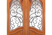 Wood Doors with Wrought Iron / Beautiful designs -- from scrollwork, to floral, to Art Nouveau -- mark this collection of Wood Doors with Wrought Iron. Made with several varieties of durable hardwood, yet featuring intricate designs within glass windows, these doors combine strength with delicate beauty.