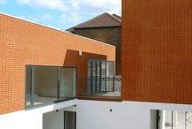 Four Interlocking Houses in London / Previously a garage workshop site, the  proposed development offers a unique and positive solution in the development of the urban environment. The project comprises of four houses which interlock to form an intimate courtyard development. Each house type is unconventional in layout. Bedrooms are on the ground floor with light-wells providing small courtyards between the bedrooms. Large oversized windows illuminate spacious double-height living rooms which occupy the first floor.