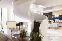 Интерьер коттеджа в стиле арт-деко / Дизайн интерьера коттеджа выполнен в манере арт-деко. Просторная, открытая гостиная объединена со столовой. С краю помещения стоит винтовая лестница на второй этаж. Основные цвета оформления белый, коричневый и серый.  При оформлении комнаты использовались живые растения.  Помещения в коттедже выглядят свежо и стильно.