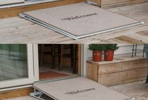 """Welcome Mat Ramp / Our Welcome Mat provides instant access! For structures with thresholds of 1"""" to 8"""", Wolfe Mobility offers ConvertaStep's """"Welcome Mat Ramp."""" When not in use, the carpet covered ramp lies flat and serves as a door mat. Simply pull a lever and the door side of the mat raises to make a ramp. The durable ramp surface is covered with a variety of carpet colors for an attractive style. No Batteries or electricity necessary."""
