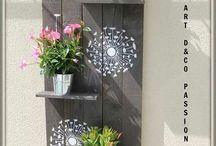 Portamacetas de madera pintada de gris con dibujos de flores blancas para colgar en la pared con estantes para las macetas