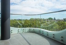 """Balustrade with Curved Glass / This project includes a number of different type of glass. The balconies are using a """" Curved toughened glass  frameless balustrade and  stainless handrail fixed on 50mm stainless standoff pins to the inside of a contoured concrete plinth upstand.  The balustrade is fully engineered curved glass system to suit the curved design of the buiding Façade""""."""