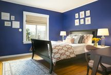 Bold blue bedroom / Bold blue Bedroom design with orange accents and wall display.