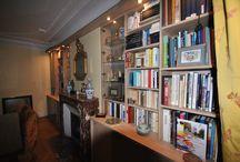 DES NICHES HABILLÉES DE BIBLIOTHEQUES / De chaque coté de la cheminée, les niches ont été équipées d'agencements mixtes, bibliothèques, vitrines, papiers, le tout coiffé d'une casquette avec spots leds. Combinaison bois et verre laqué noisette. Conception sur mesure.